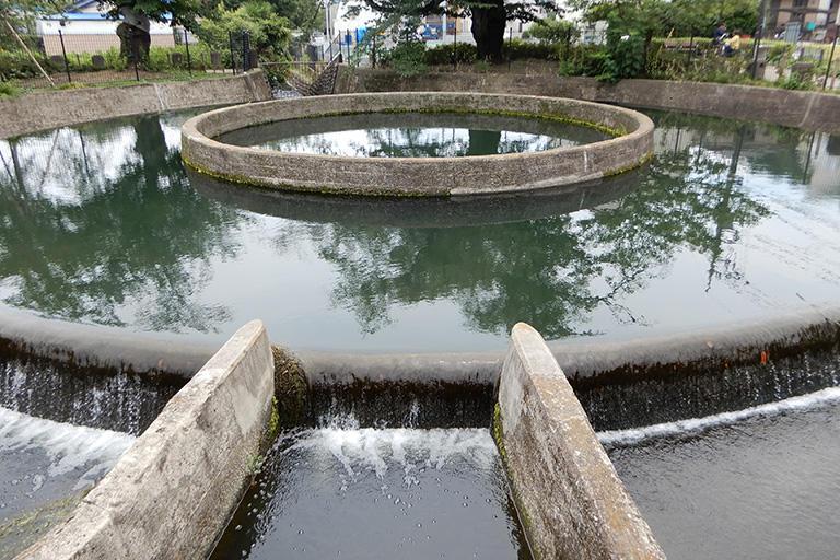 神奈川県の二ヶ領用水につくられた久地円筒分水。円筒の中心から吹き出した水が外側の円筒に沿って溢れ、4つの堀に導かれる仕組み。円周を田の灌漑面積の比率で仕切って公平に水を分けたことで、長年の水騒動が解決