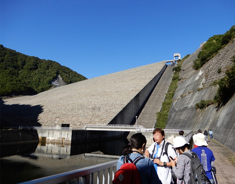 石を積み上げてつくられたロックフィルダムは、穏やかな表情。右側の放水路から水を放流する(群馬県にある奈良俣ダム)