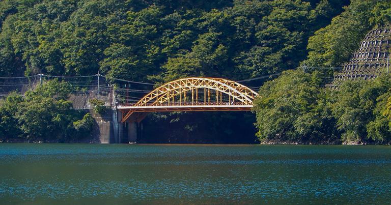 奥多摩湖に架かる中路式の鋼アーチ橋。三日月型のアーチの中間部分に道路が通っている(奥多摩湖の麦山橋)