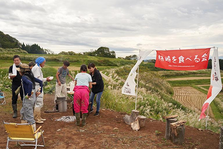 稲刈りの後はプロジェクトのメンバー全員で、地元の新米を炊いて昼食。かなたに頚城山塊と日本海を臨む絶景の休憩場所で、農業談義に花が咲く。