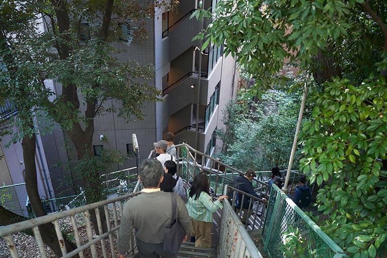 愛宕神社の裏参道を下りる。崖に寄り添う階段は、愛宕山の