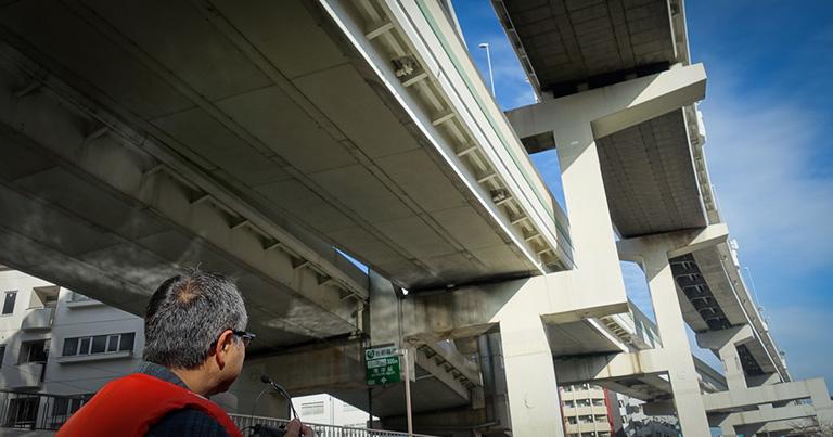 説明するマツこと松永昭吾さん。高架橋が上下2段になっている箇所では、高い方の裏面に吸音板が貼られている