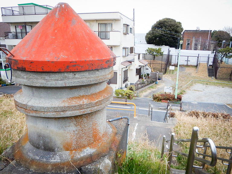 """解散後、""""面白いモノ""""が見られるというので、有志の方々に着いて浄水所裏手の多摩川土手へ。赤いトンガリ帽子の塔は、「取水管の空気抜き」。画面奥に見える茶色の建物が浄水所のポンプ室。"""