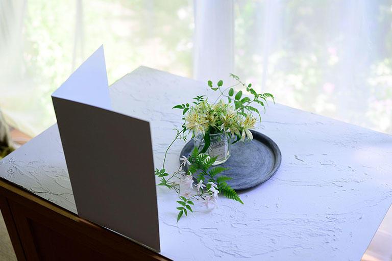 レースのカーテンを引いた窓辺に花を置いて、窓に向かって撮ります。