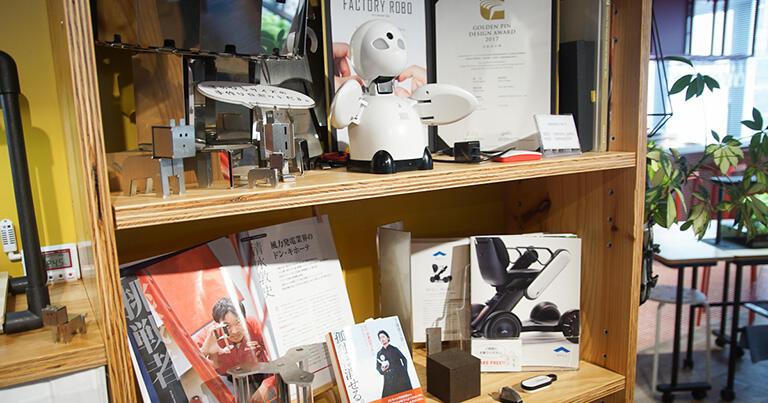 棚の上段にあるロボットがオリィ研究所の分身ロボット「OriHime」、棚の下段の右端にあるのが電動車椅子WHILLのカタログ。