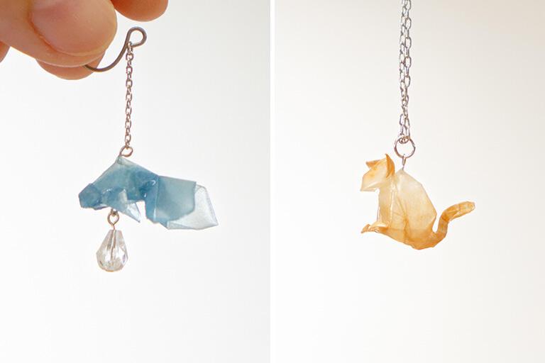 有澤悠河 作 (左)「金魚」ピアス・イヤリング、(右)「ねこ」ネックレス。折り紙作品を樹脂でコーティングしてアクセサリーにしている