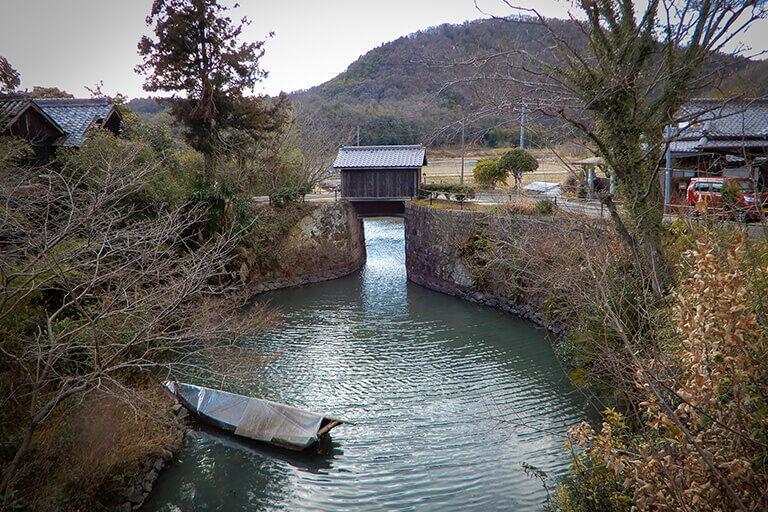 県道側から倉安川側を見る。紡錘形の閘室の奥に「二の水門」がある。住宅のような上屋は「巻き上げ機室」。水門のゲートを上げ下げする装置が格納されている。