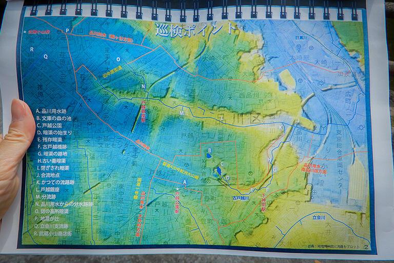 戸越フィールドワークの地図。中央下の戸越公園からアルファベット順に巡り、左上の武蔵小山駅まで歩いた。3Dの地図に流路をプロットしてある。オレンジ色の線は人工的な用水路、青い線は自然河川を示している