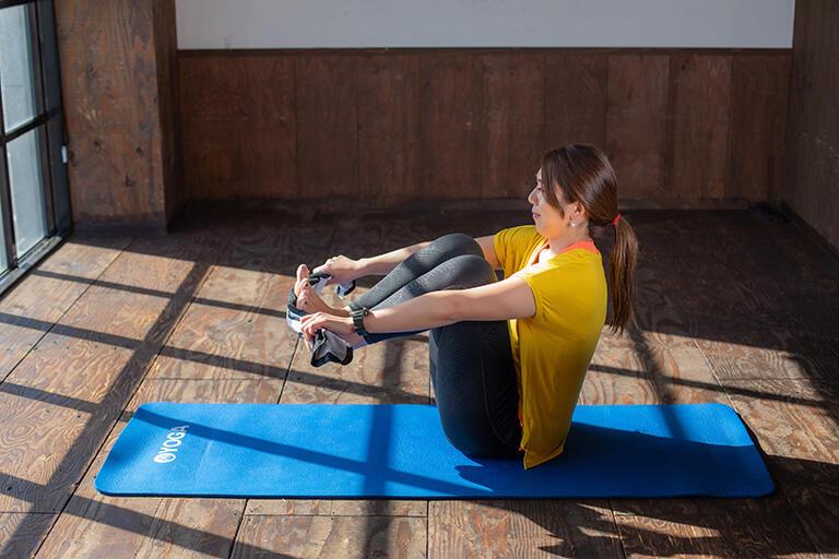 ②その状態からタオルの下側で足をそろえたまま伸ばします。次にタオルの上側に足を移動してそろえたまま脚を伸ばします。タオルの上側の場合は腕が胸の位置だと難しいので、腕を少し下げてみましょう。それを上下で繰り返していきます。