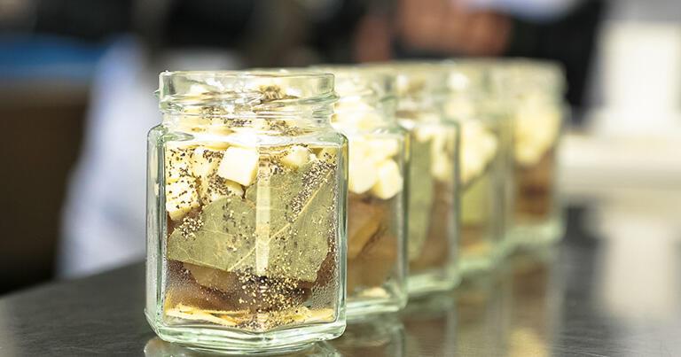 瓶の中にいぶりがっこ、チーズ、ローリエなどをハーバリウムのように美しく配置する