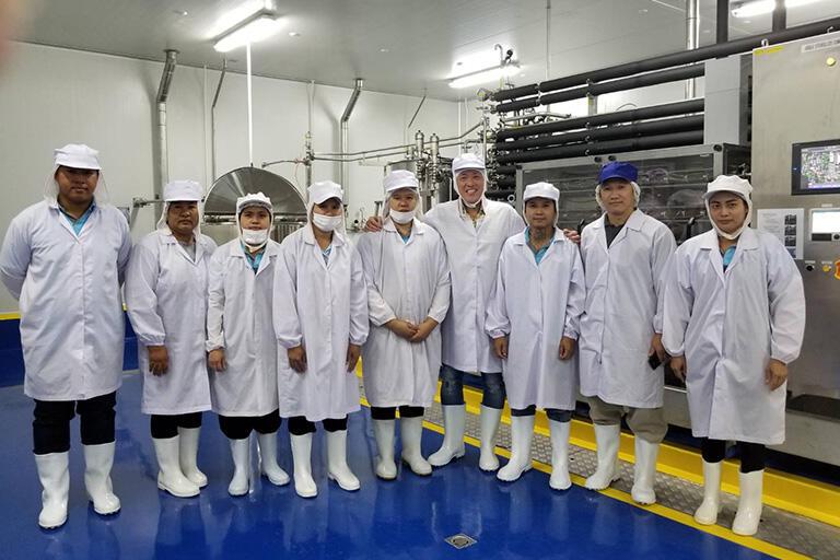 タイ工場のスタッフと本間さん。後ろに見えているのが工場の心臓部である「ジュール加熱機」