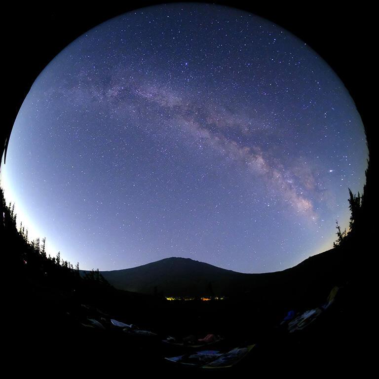 ツアーでは寝転んで星空を楽しむことも。魚眼レンズを使って撮影した富士山と天の川(撮影:武田康男)