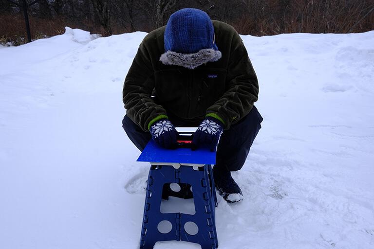 デジタルカメラの顕微鏡モードで撮影中の武田さん。青い板の上に雪の結晶、その上にカメラを乗せてシャッターを押すだけ(撮影:武田康男)