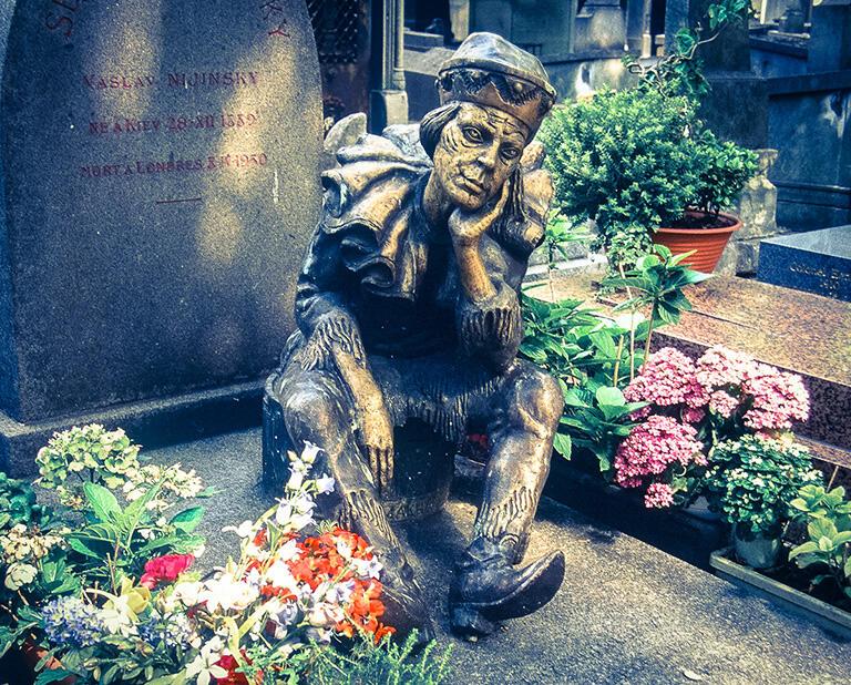 今も花がたむけられているモンマルトル墓地のニジンスキーの墓。彼が着ているのは「ペトリューシカ」の衣装だ
