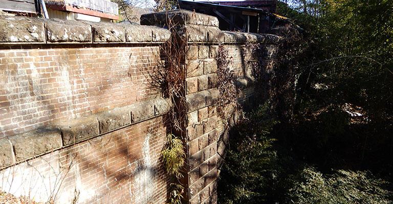 旧甲州街道に残る大原トンネルの跡。画面中央の壁柱の右側に、抗口のアーチがかすかに見える